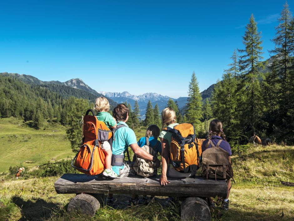 Sie sehen eine Familie bei einer Wanderpause im Salzburger Land mit herrlichem Bergpanorama. JUFA Hotels bietet erholsamen Familienurlaub und einen unvergesslichen Winter- und Wanderurlaub.