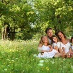 Eine Familie mit drei Kindern sitzt auf einer Blumenwiese zwischen Bäumen. JUFA Hotels bietet kinderfreundlichen und erlebnisreichen Urlaub für die ganze Familie