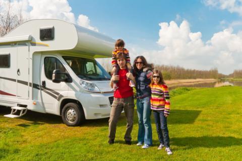 Eine Familie steht vor einem Wohnwagen auf einer Wiese im Sommer. JUFA Hotels bietet kinderfreundlichen und erlebnisreichen Urlaub für die ganze Familie.