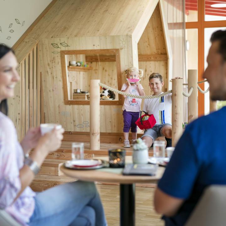 Sie sehen Kinder im Spielhaus sitzen und die Eltern im Vordergrund im JUFA Hotel Waldviertel. Der Ort für erholsamen Familienurlaub und einen unvergesslichen Winter- und Wanderurlaub.