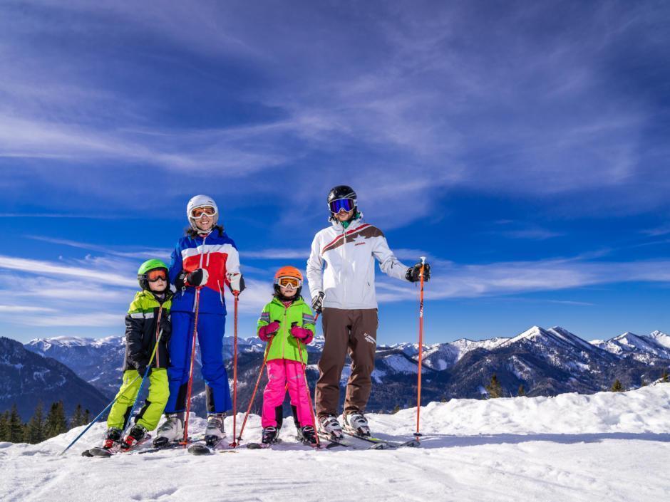 Sie sehen eine Familie auf der Skipiste mit Bergpanorama zum Foto aufgestellt auf der Mariazeller Bürgeralpe. JUFA Hotels bietet erholsamen Familienurlaub und einen unvergesslichen Winterurlaub.