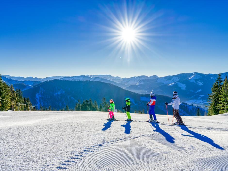 Sie sehen eine Familie beim Skifahren mit Sonne und Bergen auf der Mariazeller Bürgeralpe. JUFA Hotels bietet erholsamen Familienurlaub und einen unvergesslichen Winterurlaub.