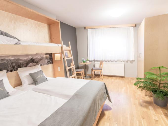 Sie sehen ein Familienzimmer im JUFA Hotel Montafon. Der Ort für erholsamen Familienurlaub und einen unvergesslichen Winter- und Wanderurlaub.