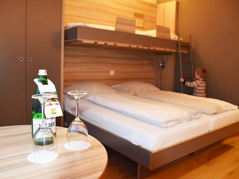 Sie sehen ein Familienzimmer mit Stockbett im JUFA Hotel Malbun – Alpin-Resort***. Der Ort für erholsamen Familienurlaub und einen unvergesslichen Winterurlaub.