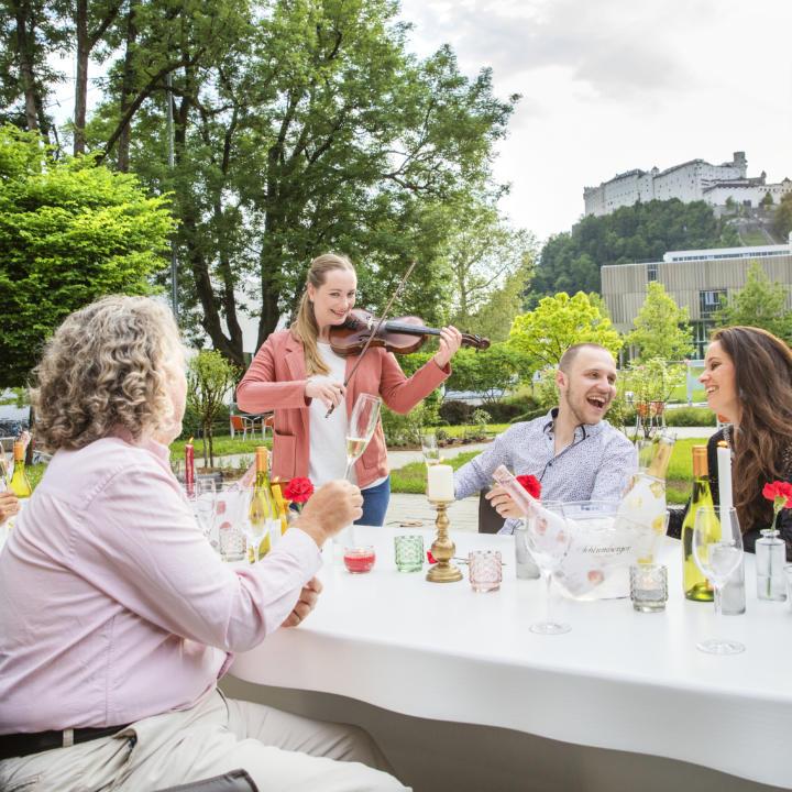 Sie sehen eine Feier am Tisch mit Musik im JUFA Hotel Salzburg City. Der Ort für erholsamen Familienurlaub und einen unvergesslichen Winter- und Wanderurlaub.