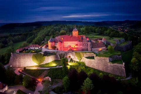 Sie sehen die Festung Rosenberg in Kronach mit Lichtern am Abend. JUFA Hotels bietet kinderfreundlichen und erlebnisreichen Urlaub für die ganze Familie.