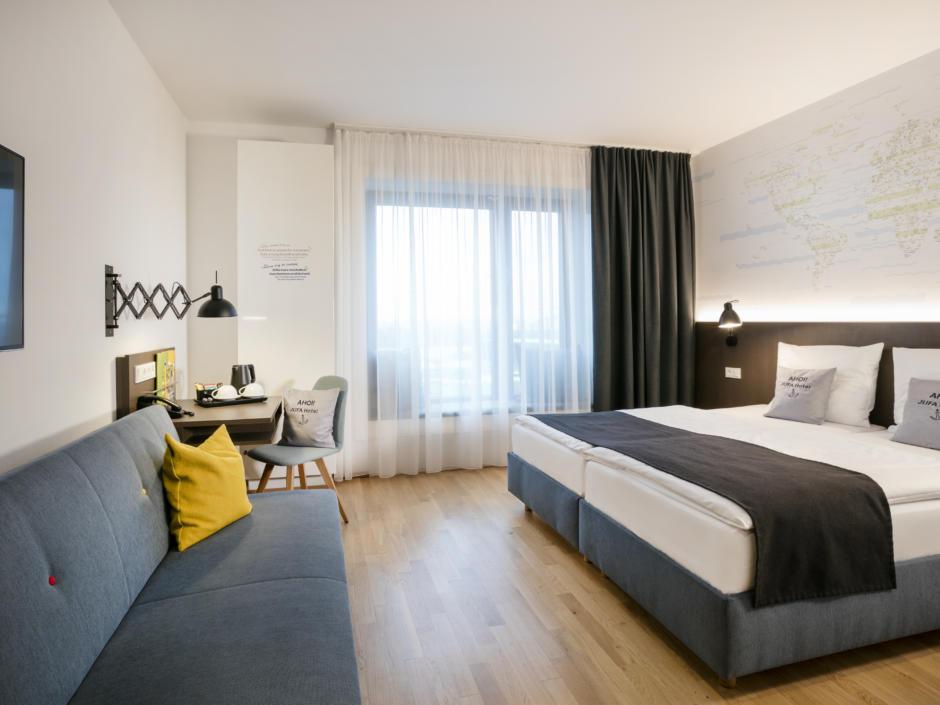 Sie sehen ein Doppelbett und eine Couch im JUFA Hotel Hamburg HafenCity. Der Ort für erlebnisreichen Städtetrip für die ganze Familie und der ideale Platz für Ihr Seminar.