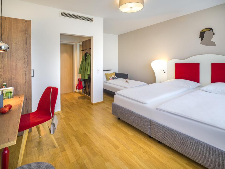 Sie sehen ein FF3 Zimmer mit Betten im JUFA Hotel Salzburg City. Der Ort für erholsamen Familienurlaub und einen unvergesslichen Winter- und Wanderurlaub.