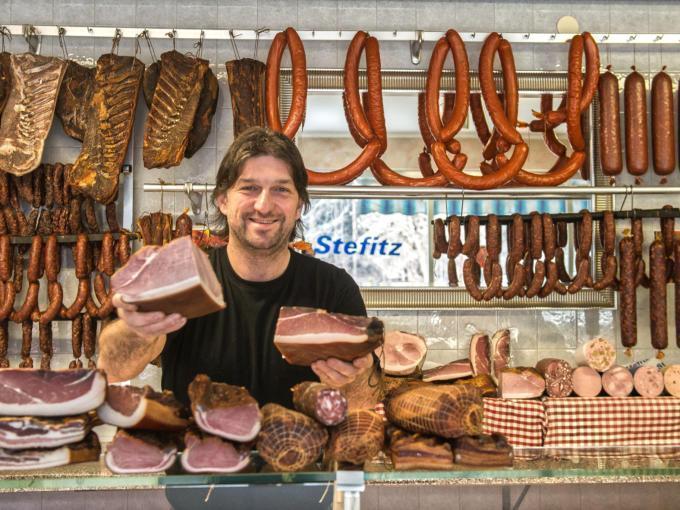 Sie sehen einen Fleischer mit Schinken von Fleischerei Stefitz. JUFA Hotels bietet kinderfreundlichen und erlebnisreichen Urlaub für die ganze Familie.