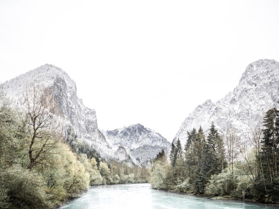 Sie sehen einen Fluss mit verschneitem Gebirge im Hintergrund im Nationalpark Gesäuse.