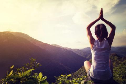 Sie sehen eine junge Frau bei der Meditation bei Sonnenaufgang auf einer Wiese in den Bergen. JUFA Hotels bietet Ihnen den Ort für erlebnisreichen Natururlaub für die ganze Familie.