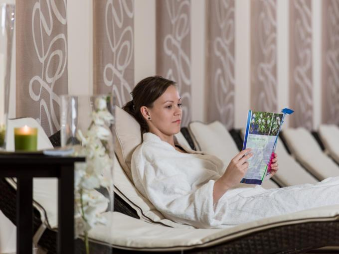 Frau liegt auf Liege und liest ein Buch im Wellnessbereich im JUFA Vulkan Thermen-Resort. Der Ort für erholsamen Thermen- und entspannten Wellnessurlaub für die ganze Familie.