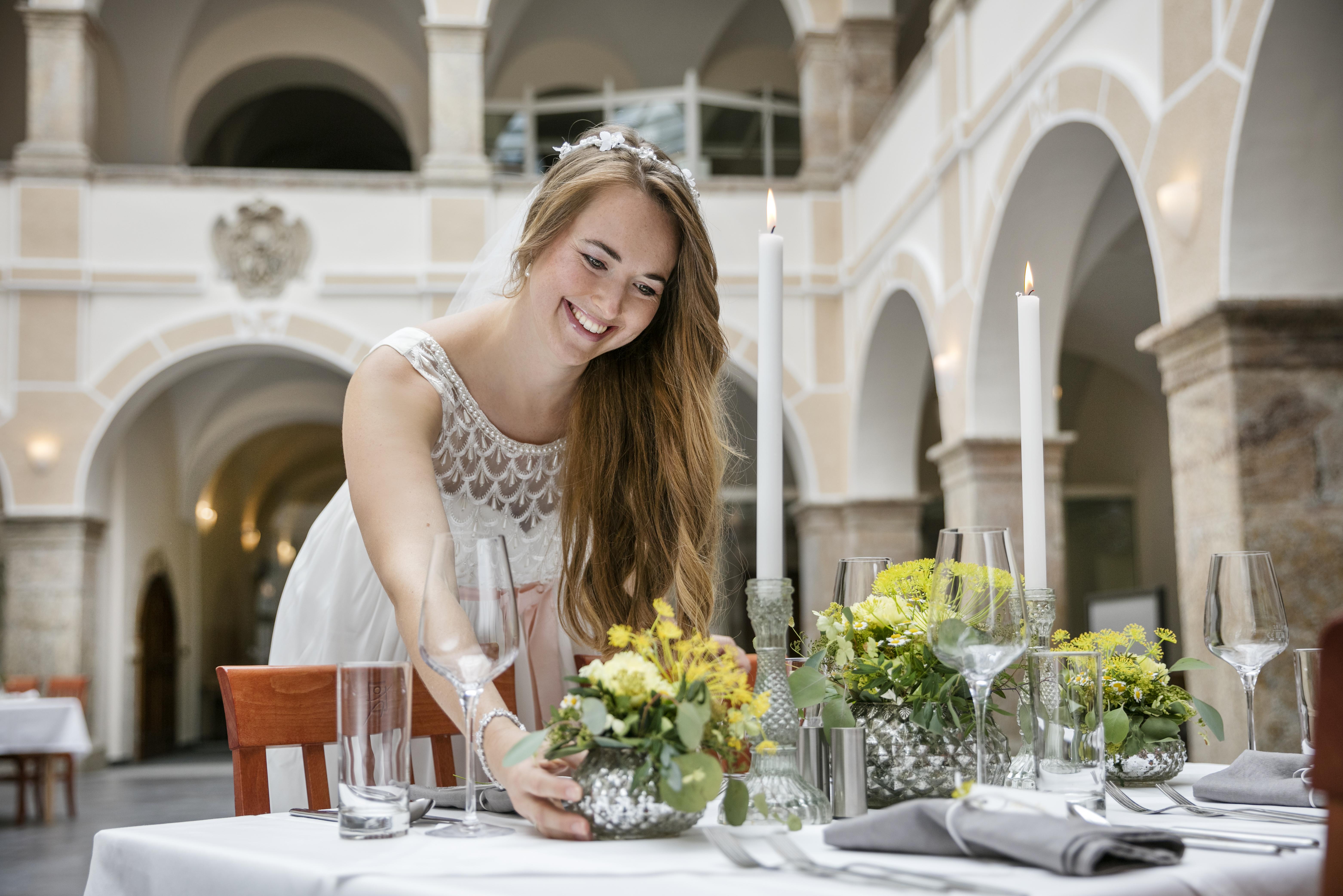 Sie sehen eine Braut den Hochzeitstisch decken im JUFA Hotel Schloss Röthelstein/Admont***. Der Ort für märchenhafte Hochzeiten und erfolgreiche und kreative Seminare.