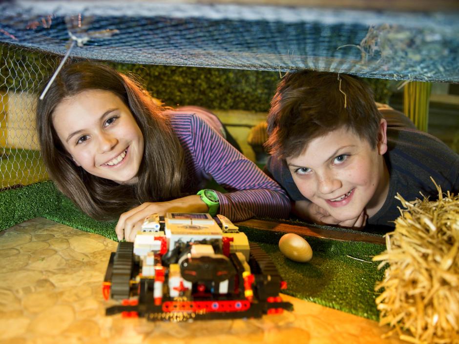 Zwei Kinder mit einem Fahrzeugroboter in der Roboterei im Grazer Kindermuseum Frida & Fred in der Nähe vom JUFA Hotel Graz City. Der Ort für erholsamen Familienurlaub und einen unvergesslichen Winter- und Wanderurlaub.