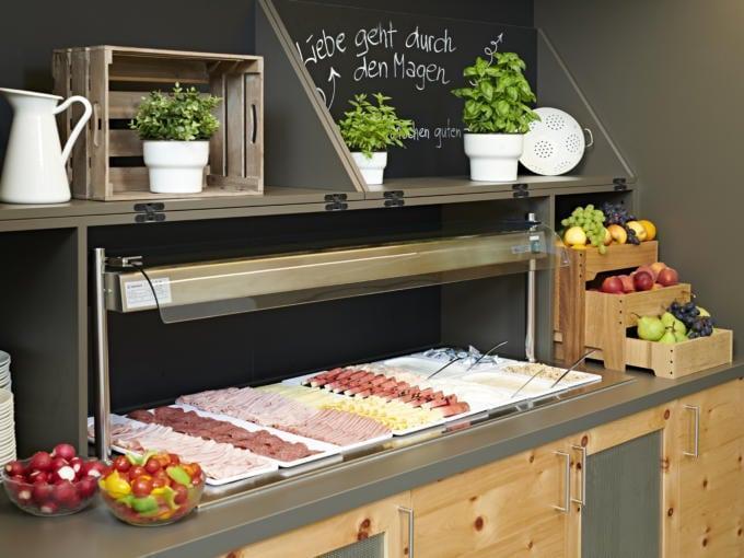 Sie sehen das reichhaltige Frühstücksbuffet mit Käse und Wurst im JUFA Hotel Stift Gurk. Der Ort für erlebnisreichen Natururlaub für die ganze Familie.
