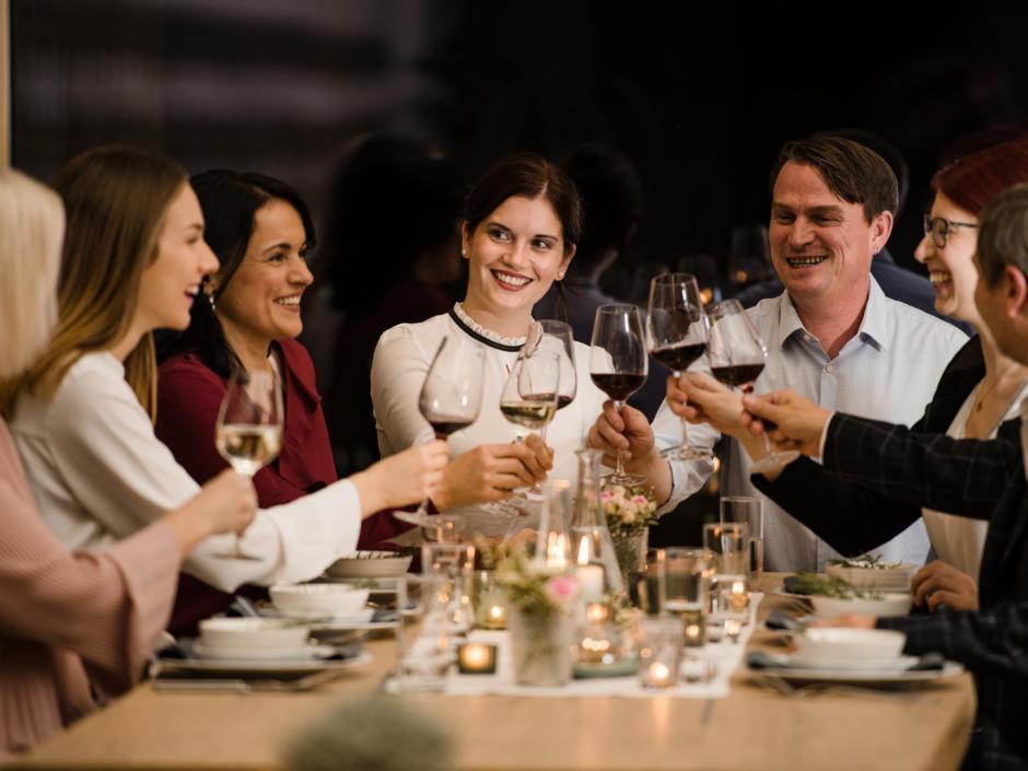 Sie sehen Gäste beim Abendessen mit Wein im EventArium am JUFA Hotel Neutal – Landerlebnis. Der Ort für erlebnisreichen Natururlaub für die ganze Familie.