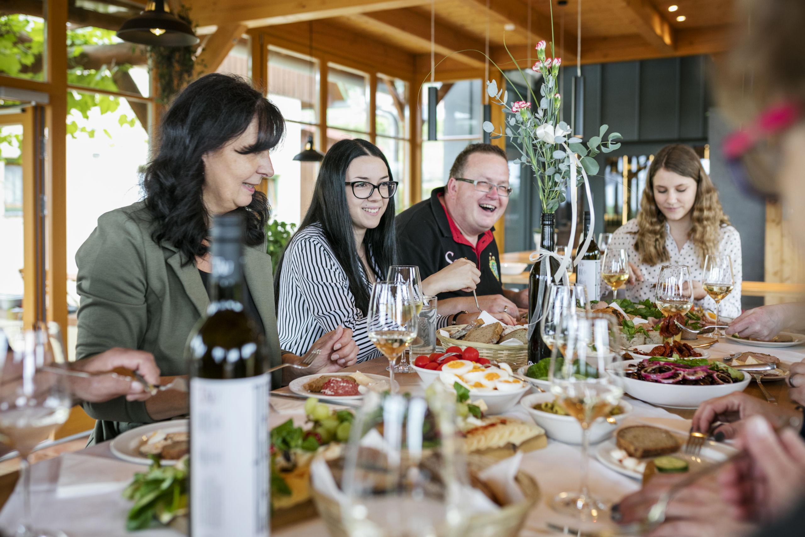 Sie sehen Gäste essen in der Vinothek & Genussladen im JUFA Hotel Tieschen – Bio-Landerlebnis. Der Ort für kinderfreundlichen und erlebnisreichen Urlaub für die ganze Familie.