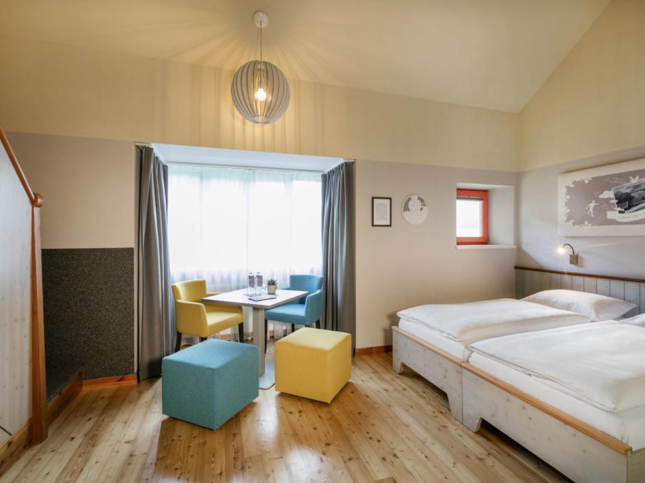 Sie sehen ein Galeriezimmer des JUFA Hotels Eisenerz. Der Ort für erholsamen Familienurlaub und einen unvergesslichen Winter- und Wanderurlaub.