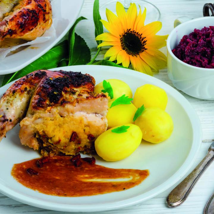 Sie sehen einen angerichteten Teller mit einer gebratenen Ganslkeule mit Kartoffeln und Rotkraut. JUFA Hotels bieten regionlae, saisonale Küche mit Zutaten aus natürlichem Anbau.