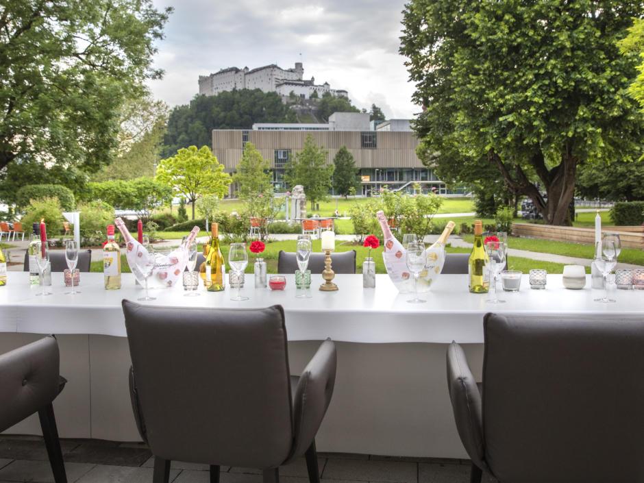 Sie sehen einen gedeckten Tisch auf der Terrasse im JUFA Hotel Salzburg City. Der Ort für erholsamen Familienurlaub und einen unvergesslichen Winter- und Wanderurlaub.