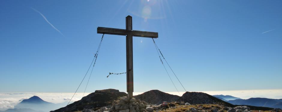 Sie sehen das Gipfelkreuz der Feistritzer Spitze auf der Petzen in Kärnten. JUFA Hotels bietet erholsamen Familienurlaub und einen unvergesslichen Winter- und Wanderurlaub.