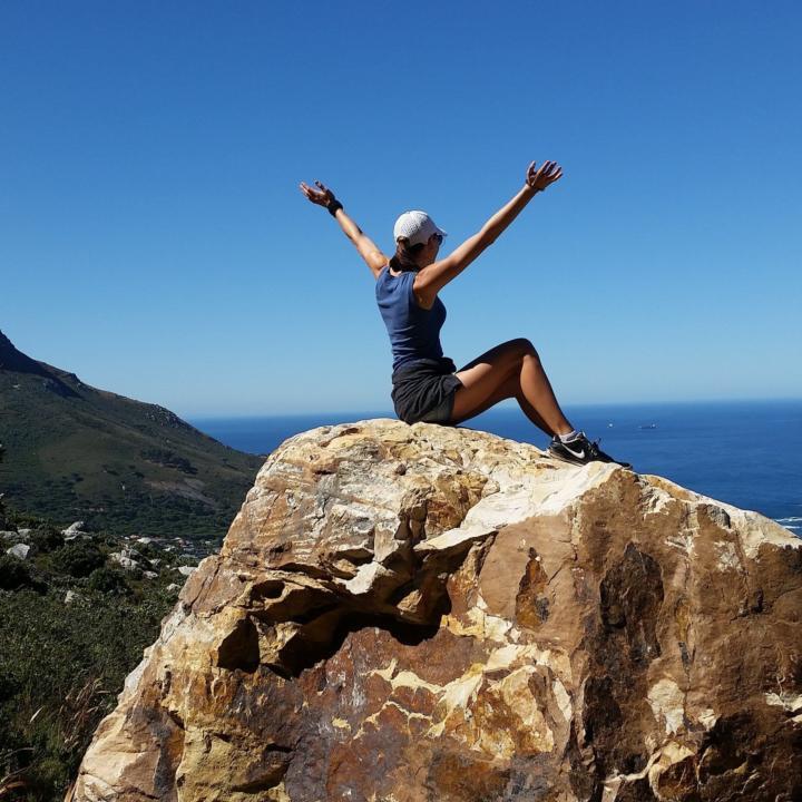 Frau sitzend auf Felsen