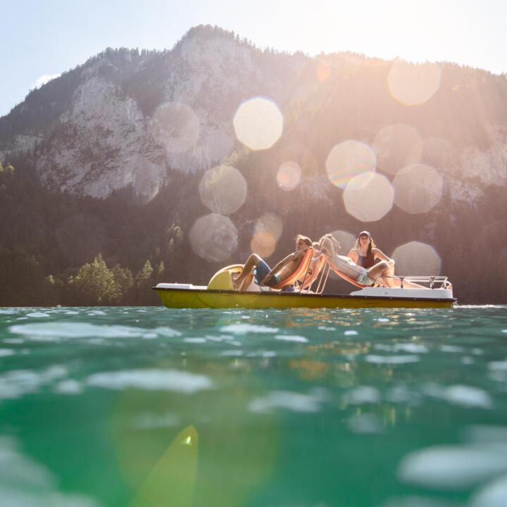 Sie sehen ein Tretboot am Gleinkersee mit Personen - unweit vom JUFA Hotel Pyhrn-Priel. Der Ort für tollen Sommerurlaub an schönen Seen für die ganze Familie.