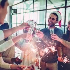 Sie sehen eine Gruppe von jungen Erwachsenen beim Sekt trinken auf einer Weihnachtsfeier. JUFA Hotels bieten Ihnen den perfekten Rahmen für Ihre Events und Feierlichkeiten.