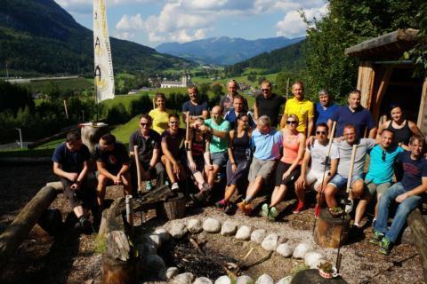 Eine Gruppe Erwachsener sitzt in Pyhrn-Priel im Wald im Outdoor Camp für ein Gruppenfoto zusammen. JUFA Hotels bietet den Ort für erfolgreiche und kreative Seminare in abwechslungsreichen Regionen.