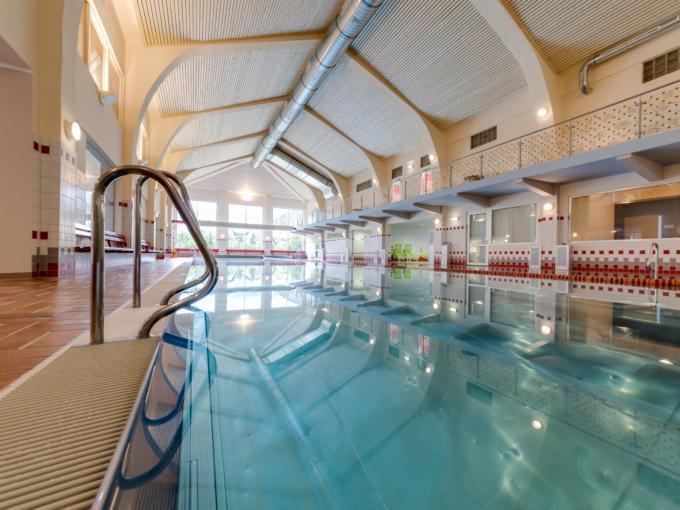 Hallenbad im JUFA Hotel Veitsch mit Beckeneinstieg auf der linken Seite des Sportbeckens. JUFA Hotels bietet kinderfreundlichen und erlebnisreichen Urlaub für die ganze Familie.