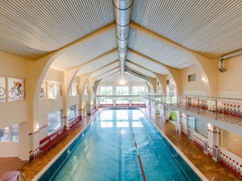Sie sehen das Hallenbad im JUFA Hotel Veitsch mit frontaler Ansicht. JUFA Hotels bietet kinderfreundlichen und erlebnisreichen Urlaub für die ganze Familie.