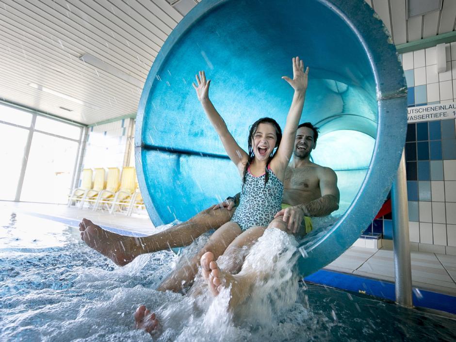 Sie sehen das Hallenbad Murau mit einer Wasserrutsche und Familie. JUFA Hotels bietet erholsamen Familienurlaub und einen unvergesslichen Winterurlaub.