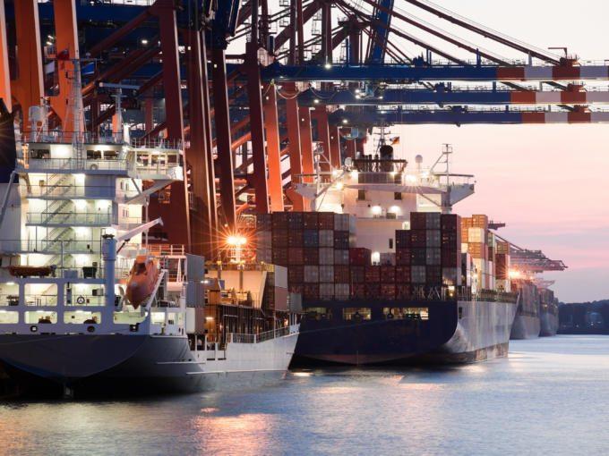 Sie sehen Containerschiffe in der Abenddämmerung im Hamburger Hafen.JUFA Hotels bietet erlebnisreichen Städtetrip für die ganze Familie und den idealen Platz für Ihr Seminar.