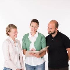 Drei Mitarbeiter vom JUFA Headoffice bei der Durchsicht von Unterlagen. JUFA Hotels bietet Ihnen einen interessanten, abwechslungsreichen Arbeitsplatz in einem tollen Team in den schönsten Regionen in Österreich, Deutschland, Liechtenstein und Ungarn.