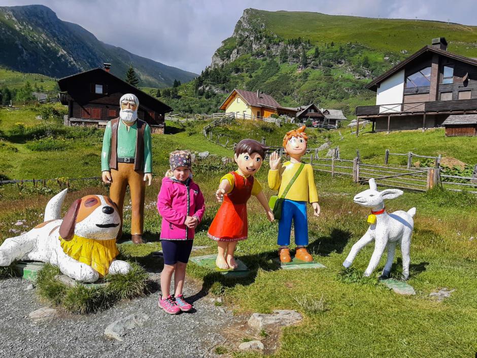 Sie sehen ein Mädchen, das vor bunten Heidi Figuren auf der Alm steht. JUFA Hotels bietet erholsamen Ski- und Wanderurlaub für Familien in Kärnten.