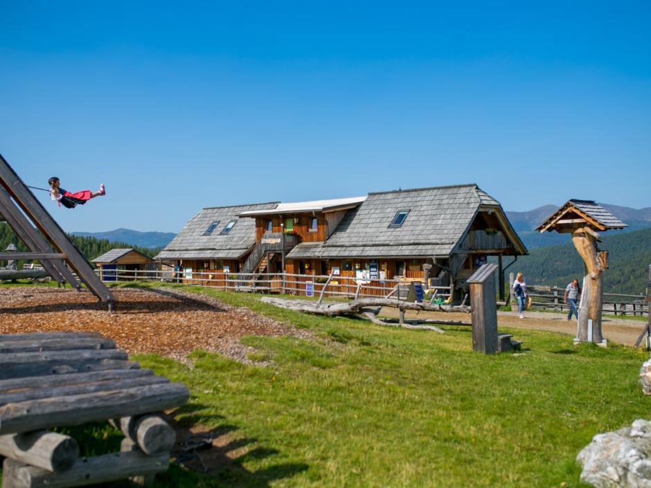 Sie sehen die Hiaslhütte mit Bergpanorama in den Nockbergen. JUFA Hotels bietet erholsamen Familienurlaub und einen unvergesslichen Winter- und Wanderurlaub.