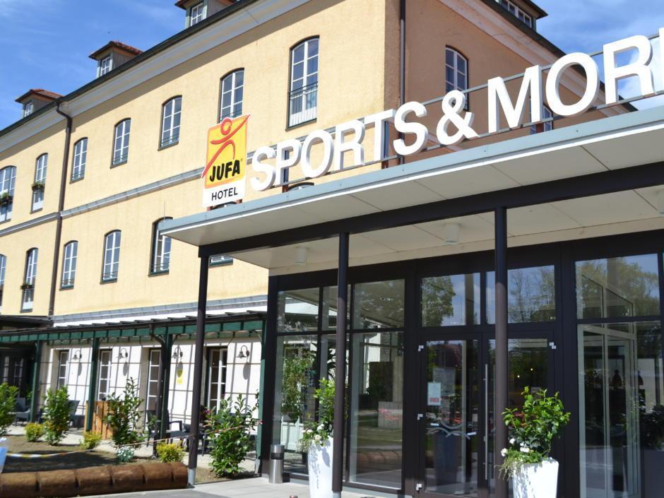 Außenansicht mit Eingang im Sommer vom JUFA Hotel Fuerstenfeld Sport-Resort. Der Ort für erfolgreiches Training in ungezwungener Atmosphäre für Vereine und Teams.