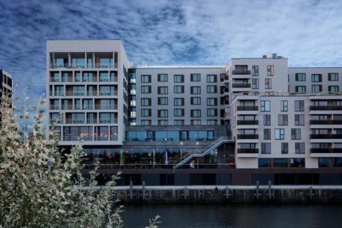 Hotelansicht vom JUFA Hotel Hamburg HafenCity an der Elbe. Der Ort für erlebnisreichen Städtetrip für die ganze Familie und der ideale Platz für Ihr Seminar.