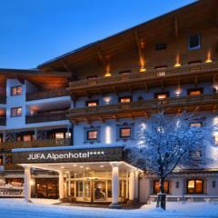 Sie sehen eine Außenansicht vom JUFA Alpenhotel Saalbach**** am Abend im Winter. JUFA Hotels bietet erholsamen Familienurlaub und einen unvergesslichen Winterurlaub.