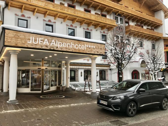Sie sehen eine Außenansicht vom JUFA Alpenhotel Saalbach im Winter. JUFA Hotels bietet erholsamen Familienurlaub und einen unvergesslichen Winterurlaub.
