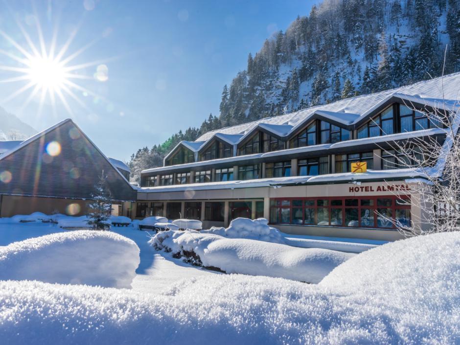 Sie sehen eine Außenansicht vom JUFA Hotel Almtal mit Sonnenschein im Winter. JUFA Hotels bietet erholsamen Familienurlaub und einen unvergesslichen Winterurlaub.