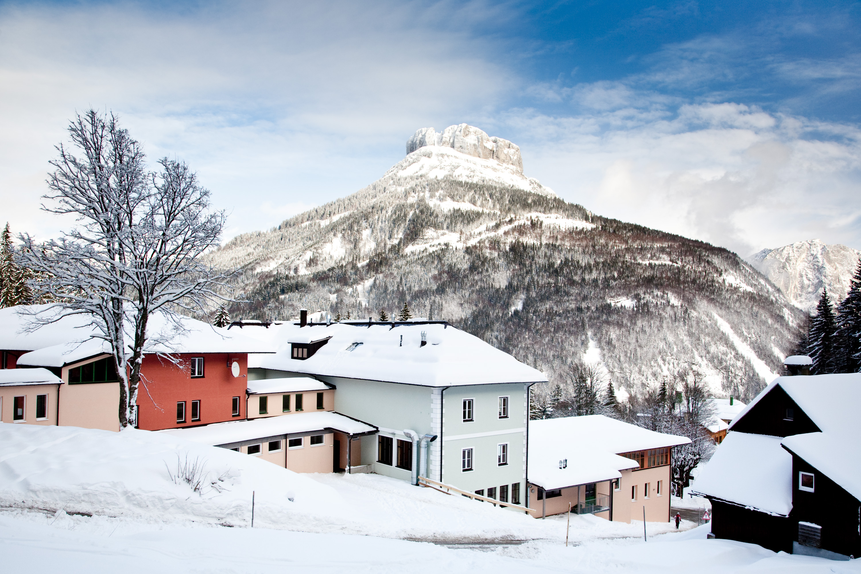 Sie sehen eine Außenansicht vom JUFA Hotel Altaussee*** mit Loser im Winter. JUFA Hotels bietet erholsamen Familienurlaub und einen unvergesslichen Winterurlaub.