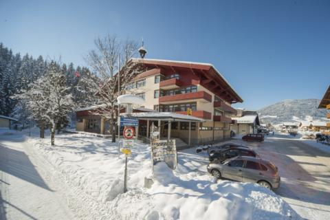 Eine Hotelansicht vom JUFA Hotel Altenmarkt mit Parkplatz im Winter. JUFA Hotel Altenmarkt, der Ort für erholsamen Familienurlaub und einen unvergesslichen Winterurlaub.