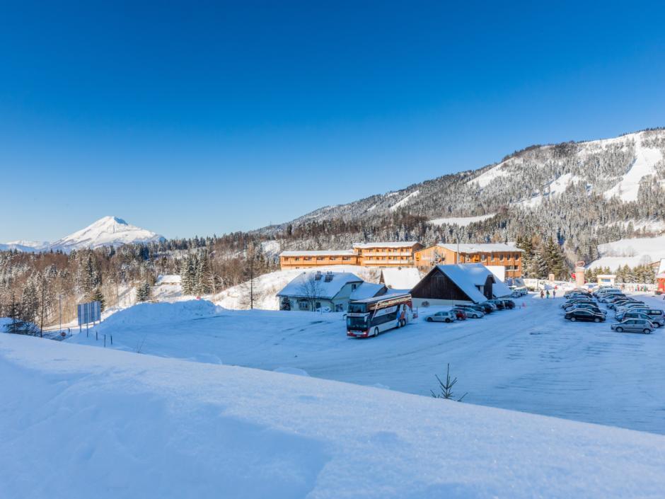 Sie sehen eine Außenansicht vom JUFA Hotel Annaberg Bergerlebnis-Resort mit Parkplatz im Winter. JUFA Hotels bietet erholsamen Familienurlaub und einen unvergesslichen Winterurlaub.