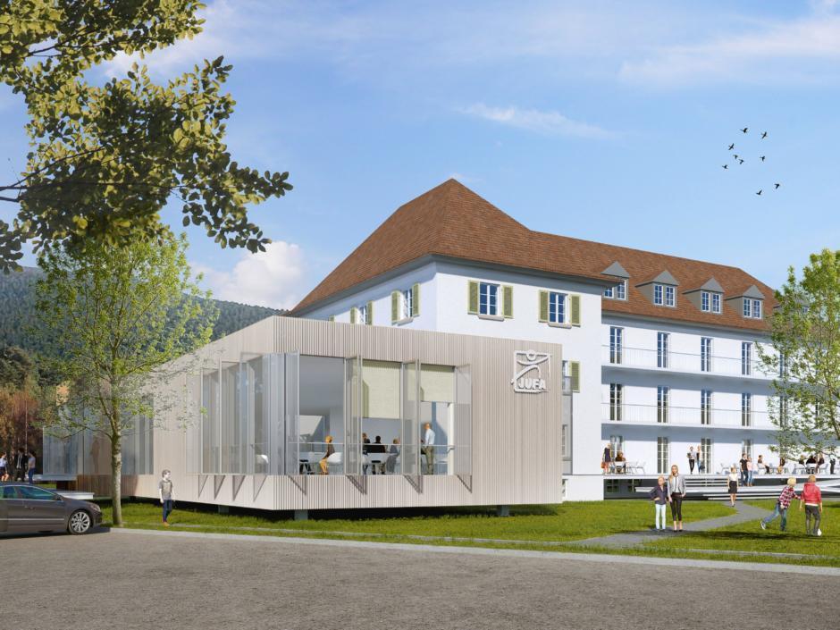 Sie sehen eine Außenansicht vom JUFA Hotel Bad Mergentheim – Taubertal mit Café im Sommer. JUFA Hotels bietet erholsamen Familienurlaub und einen unvergesslichen Winter- und Wanderurlaub.