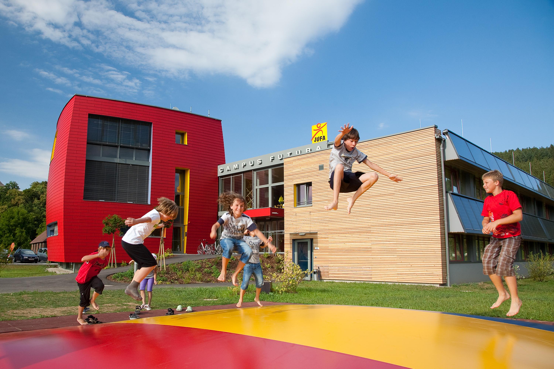 Sie sehen eine Außenansicht vom JUFA Hotel Bleiburg/Pliberk – Sport-Resort mit Kindern im Sommer. JUFA Hotels bietet Ihnen den Ort für erfolgreiches Training in ungezwungener Atmosphäre für Vereine und Teams.
