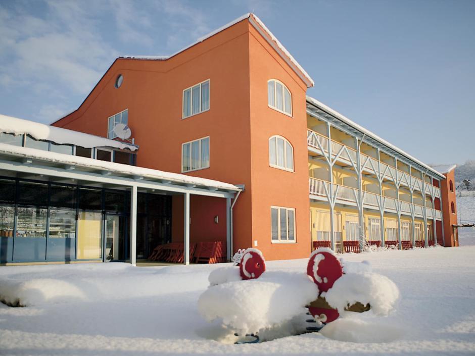 Aussenansicht mit Balkonfront im Winter vom JUFA Hotel Gnas - Sport-Resort. Der Ort für erfolgreiches Training in ungezwungener Atmosphäre für Vereine und Teams.