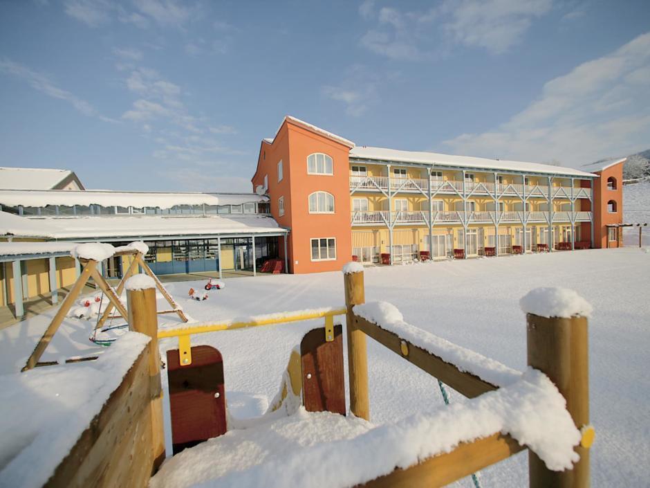Aussenansicht mit Spielplatz im Winter vom JUFA Hotel Gnas - Sport-Resort. Der Ort für erfolgreiches Training in ungezwungener Atmosphäre für Vereine und Teams.