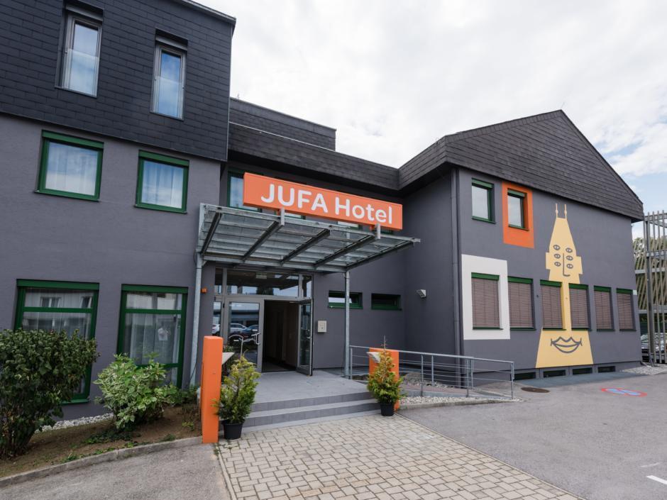 Sie sehen eine Außenansicht des JUFA Hotels Graz-Süd mit Rollstuhlrampe. JUFA Hotels bietet erlebnisreichen Städtetrip für die ganze Familie und den idealen Platz für Ihr Seminar.