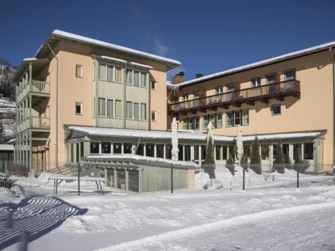Aussenansicht mit Sonnenterrasse im Winter vom JUFA Hotel Kaprun. Der Ort für erholsamen Familienurlaub und einen unvergesslichen Winter- und Wanderurlaub.